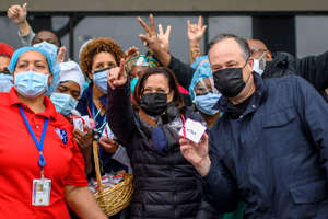 a group of people posing for the camera: Vice President Kamala Harris, center, and her husband, Second Gentleman Doug Emhoff, pose for a picture with healthcare workers at the Washington, DC, VA Center, a veterans hospital, as they delivered baskets of Valentine's cookies on Feb. 13, 2021.