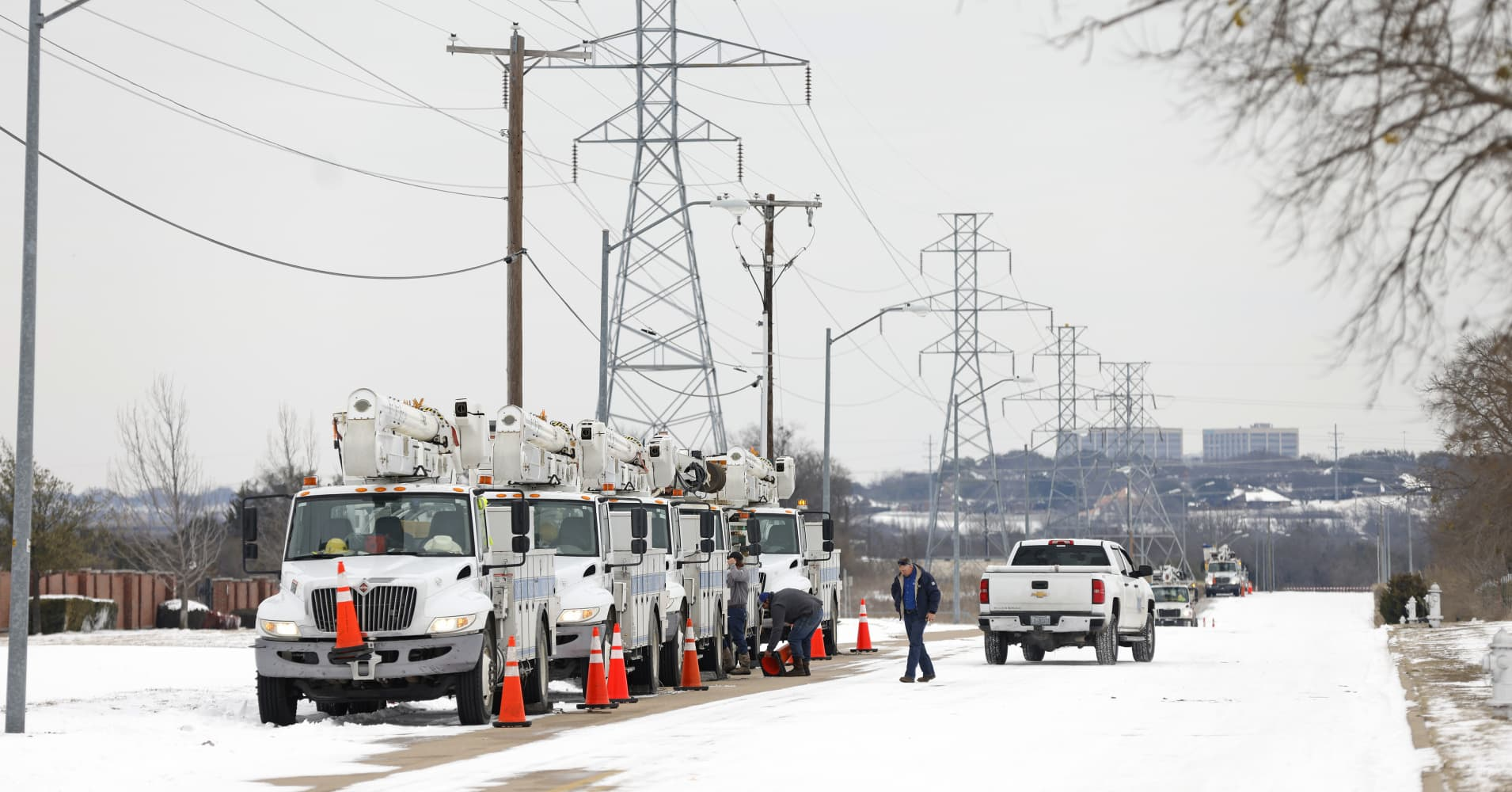 a group of people standing on top of a snow covered road: Pike Electric service trucks line up after a snow storm on February 16, 2021 in Fort Worth, Texas. Winter storm Uri has brought historic cold weather and power outages to Texas as storms have swept across 26 states with a mix of freezing temperatures and precipitation.