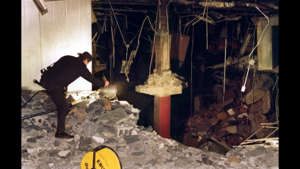 a person standing next to a fireplace: NEW YORK, NY - FEBRUARY 28: A police photographer adjusts a light at the edge of the crater in an underground parking garage at the World Trade Center 28 February 1993. The explosion killed 05 people and injured over 1,000. AFP PHOTO MARK D. PHILLIPS /Getty Images)