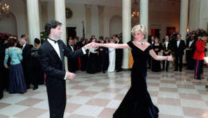 "Diana, Princess of Wales et al. standing in a room: In 1985, at the White House, John was able to show off his 'Saturday Night Fever' dance moves with Princess Diana. The Princess asked John to dance with her, she later named the dress she wore on that night the ""Travolta Dress."""