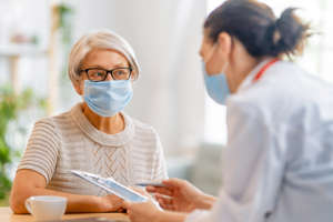 a woman looking at her cell phone: Doctor and senior woman wearing facemasks