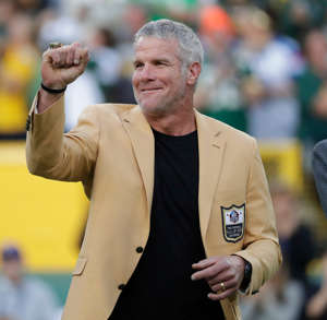 Brett Favre wearing a suit and tie: Brett Favre shows off his Pro Football Hall of Fame ring after receiving it during a 2016 game at Lambeau Field.