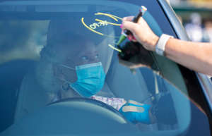 Edith Kelly gets her COVID vaccine as a worker writes her observation time on her windshield on Sunday, Feb. 21, 2021, at the STARS Complex in Fort Myers.