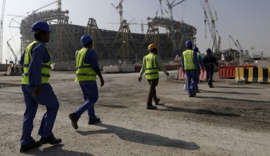 Workers walk to the Lusail Stadium, one of the 2022 World Cup stadiums, in Lusail, Qatar, Friday, Dec. 20, 2019. Construction is underway to complete Lusail's 80,000-seat venue for the opening game and final in a city that didn't exist when Qatar won the FIFA vote in 2010. (AP Photo/Hassan Ammar)