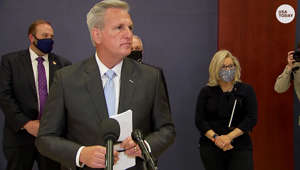 Kevin McCarthy et al. standing next to a person in a suit and tie