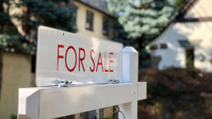 a sign on the side of a building: Real estate for sale sign in residential neighborhood, New Jersey, USA.