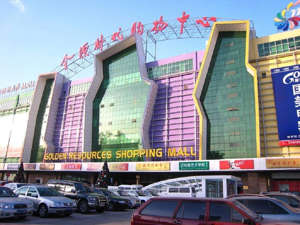 a car that has a sign on the side of a building: With more than 1,000 stores spread across 560,000 square metres (six million square feet) and six floors, China's Golden Resources Shopping Mall is one-and-a-half times bigger than the largest shopping mall in the United States. Inaugurated in 2005, the mall is also known as the