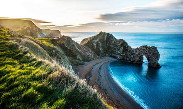 Slide 2 of 52: This beach along the Jurassic Coast in Dorset, England, is famous for its Durdle Door, a stone archway created when the ocean tunneled through the limestone about 10,000 years ago.
