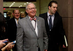 a group of people standing next to a person in a suit and tie: Rep. Ron Wright, a Texas Republican who had battled health challenges over the past year including lung cancer treatment died Sunday, Feb. 7, 2021, more than two weeks after contracting COVID-19, his office said Monday, Feb. 8. He was 67.