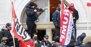 a group of people standing in front of a crowd: A man breaks a window as a mob of supporters of U.S. President Donald Trump storm the U.S. Capitol Building in Washington, January 6, 2021.
