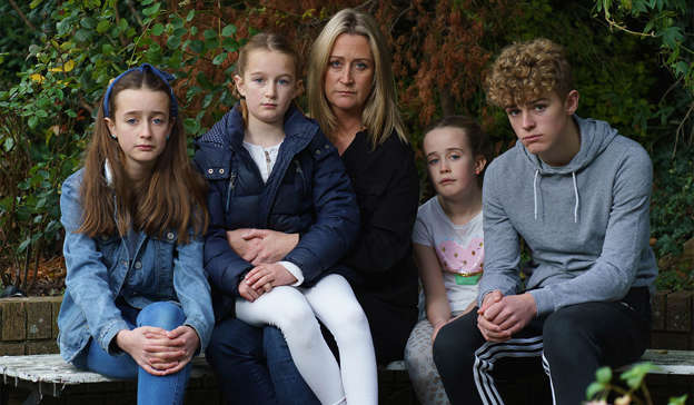 a couple of people that are sitting on a bench posing for the camera: Richard O'Halloran's wife Tara with children Amber, Scarlett, Isabella and Ben. Pic: Fran Veale