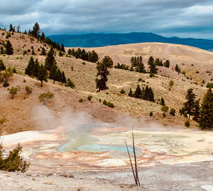 a body of water with a mountain in the background: Yellowstone's hot pots and fumaroles are more fun without the crowds. (Photo courtesy of Melanie Haiken)