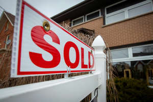 a sign in front of a building: The Calgary Real Estate Board's September report shows that the city's real estate market continues to heat up, with the average price of a home up 8.6 per cent since last year.