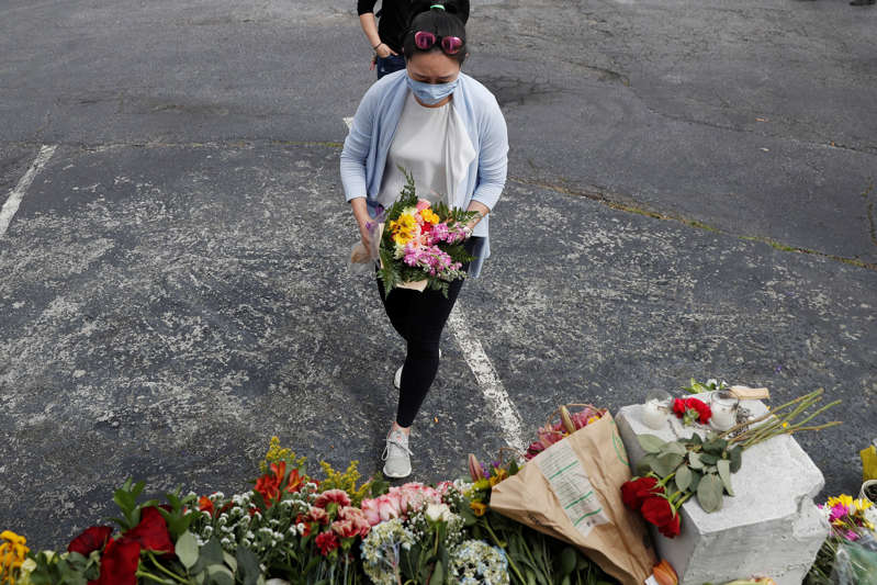 Sarah Tang, 31, lays flowers at a makeshift memorial outside the Gold Spa following the deadly shootings in Atlanta, Georgia, U.S. March 19, 2021. REUTERS/Shannon Stapleton