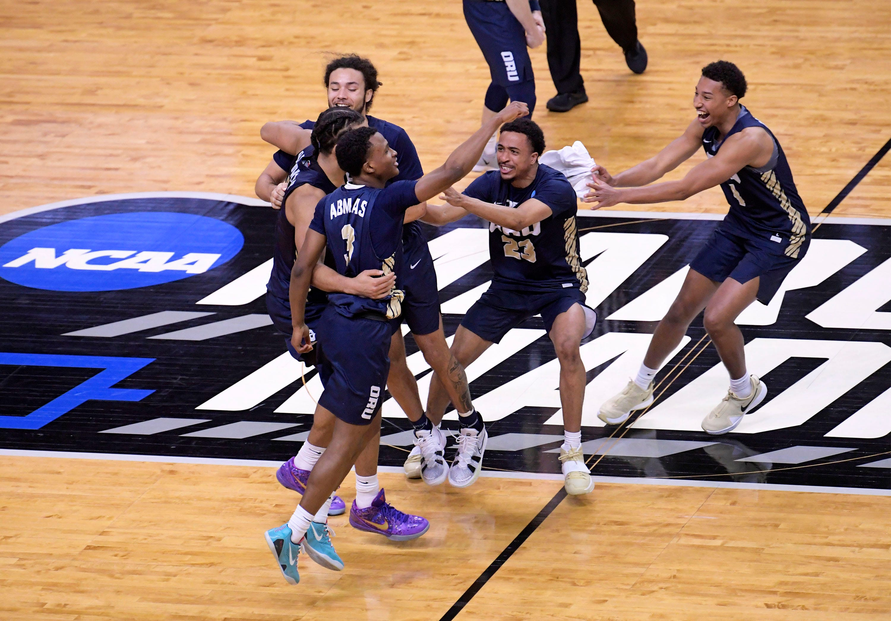 a group of people on a court: Second round: The Oral Roberts Golden Eagles celebrate their 81-78 victory over the Florida Gators at the Indiana Farmers Coliseum.