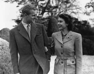 Elizabeth II wearing a suit and tie standing next to a woman: Princess Elizabeth and her husband Prince Philip, Duke of Edinburgh enjoying a romantic walk during their honeymoon at Broadlands in Romsey, Hampshire, in November 1947. Elizabeth became queen in 1952. Her marriage is the longest of any British sovereign.