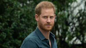 Prince Harry standing in front of a forest