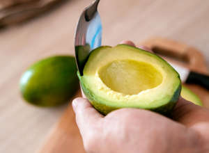a hand holding a piece of fruit: scoop avocado out of peel cut