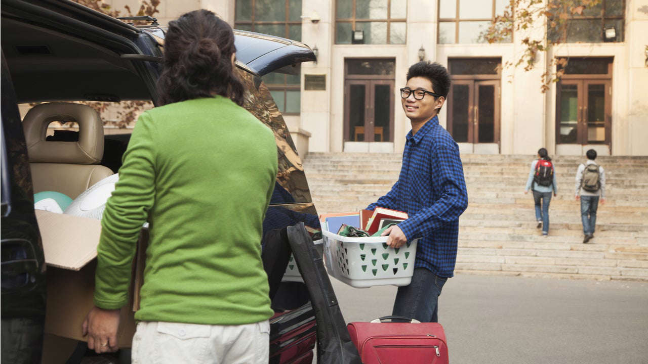 a person holding a piece of luggage: Parents help college student move into dorms