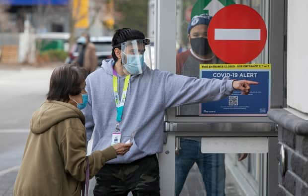 a man holding a sign: A health care worker directs a Toronto resident to a COVID-19 mass vaccination clinic at the East York Town Centre mall in the city's Thorncliffe Park neighbourhood on March 24, 2021.