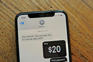 a stereo sitting on top of a wooden table: You can use Apple Cash to pay people through the Messages app on your iPhone. Patrick Holland/CNET