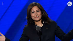 Neera Tanden standing in front of a stage