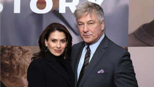 a person standing in front of Hilaria Baldwin, Alec Baldwin posing for the camera