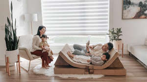 a person sitting in a living room: Photo of a family lounging and reading books on a modular play couch