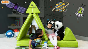a group of stuffed animals sitting on top of a desk: Photo of two kids playing on a modular play couch set up like a space ship