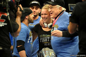 Ronda Rousey standing in front of a crowd: Dec. 6, 2012, promoted to undisputed UFC champion after Strikeforce purchase. ... 6 title defenses.