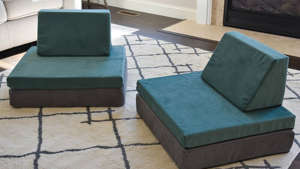 a living room with a couch and a table: Photo of a modular kids couch set up as two chairs on a rug