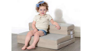a young boy sitting on a bed: Photo of a toddler sitting on a foldable cushion couch