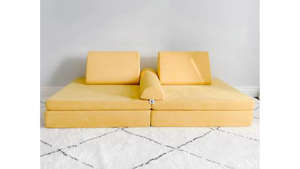 a close up of furniture: Photo of a yellow play couch on a rug