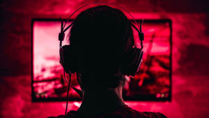 a close up of a man in a dark room: Woman wearing headphones playing video games late at night