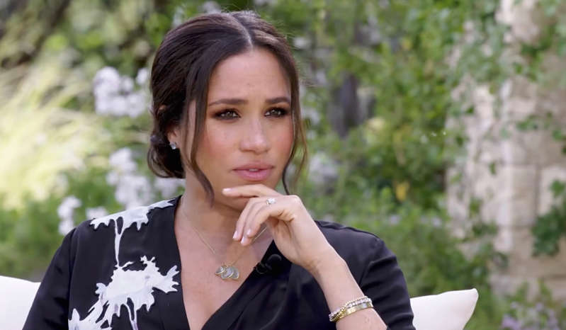 Meghan Markle talking on a cell phone: Meghan refused to name the identity of the 'royal racist' as it would be too 'damaging' for them, but Oprah later said Harry told her it was not his grandmother the Queen or his grandfather, the late Prince Philip. Pic: CBS/Meghan and Harry: A Primetime Special