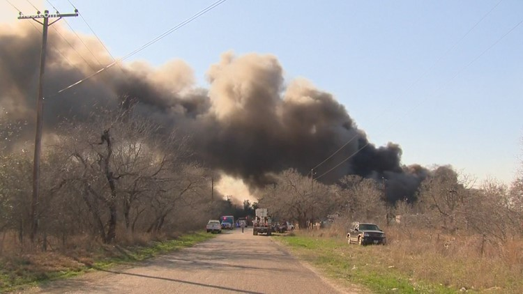 a train is parked on the side of a road: Huge plumes of smoke erupt in rural Atascosa Co. fire
