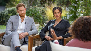 Prince Harry, Meghan Markle sitting at a table