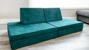 a blue and green bed in a room: Photo of a play couch set up in a living room