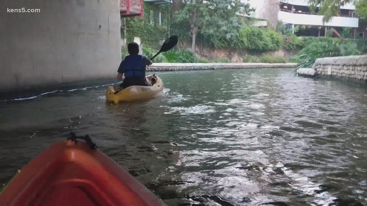 a man riding on the back of a boat in the water: River Walk kayaking program extended