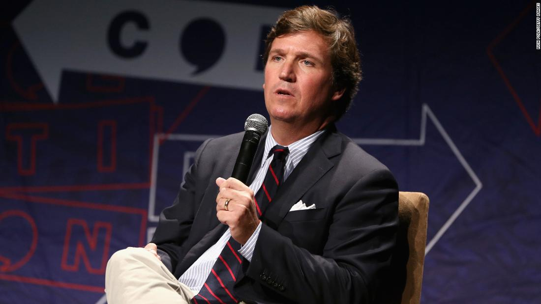 Tucker Carlson wearing a suit and tie: LOS ANGELES, CA - OCTOBER 21: Tucker Carlson speaks onstage during Politicon 2018 at Los Angeles Convention Center on October 21, 2018 in Los Angeles, California. (Photo by Rich Polk/Getty Images for Politicon )