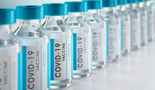 Row Covid-19 or Coronavirus vaccine flasks on white background