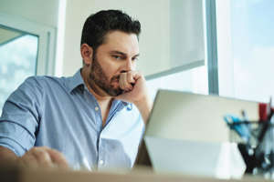a man looking at the camera: Angry Hispanic businessman working with laptop computer in office, losing patience. Anxious executive man under stress at work for technology problems and software pc virus.
