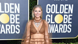 Gwyneth Paltrow standing in front of a sign