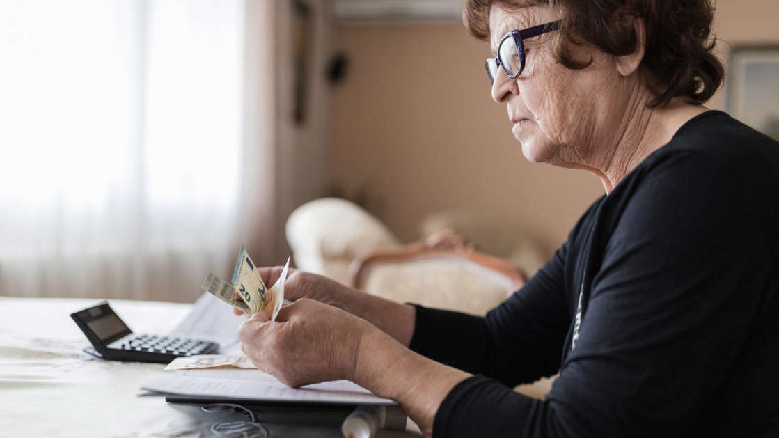 a man sitting at a table using a laptop: Senior woman holding money in her hands at home
