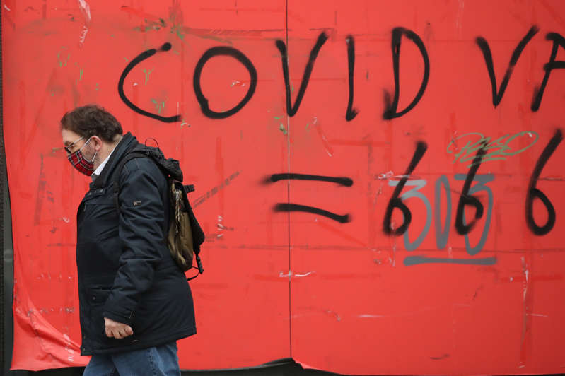A man walks past coronavirus graffiti in Edinburgh where stricter lockdown measures for mainland Scotland are now in force. (Photo by Andrew Milligan/PA Images via Getty Images)