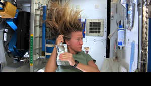 a woman taking a selfie: There are many challenges associated with living on the International Space Station. Things that are easy to do on Earth where there is gravity can be difficult in space, for astronauts have been living for more than a decade aboard the space station and have developed a few tricks that make these everyday tasks easier. Expedition 36 Flight Engineer Karen Nyberg shows how she washes and rinses her hair in microgravity aboard the International Space Station  For more about the softer side of space, visit:  http://www.nasa.gov/mission_pages/station/expeditions/expedition36/nyberg_profile.html  Follow Nyberg on social media at:   https://twitter.com/AstroKarenN or @AstroKarenN http://pinterest.com/knyberg/ https://www.facebook.com/AstronautKarenNyberg  HD download link: https://archive.org/details/NybergShampoo