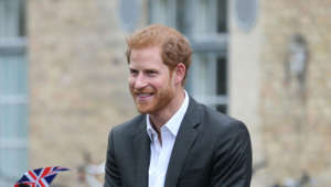Prince Harry wearing a suit and tie talking on a cell phone