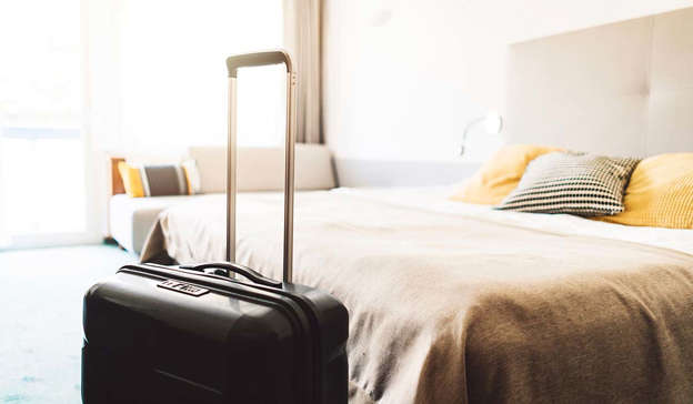 a pile of luggage sitting on top of a bed: Hotel prices in the capital have surged ahead of Sunday's All Ireland final. Pic: Getty Images