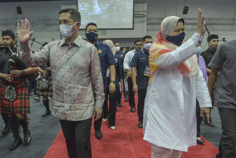 a group of people standing in front of a crowd: Datuk Seri Azmin Ali and Zuraida Kamaruddin arrive during the 'National Congress: Unite For Malaysia' event at Malaysia International Trade & Exhibition Centre in Kuala Lumpur, August 22, 2020. — Picture by Shafwan Zaidon