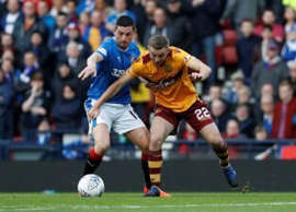 a football player kicking a ball in front of a crowd: allan campbell dorrans